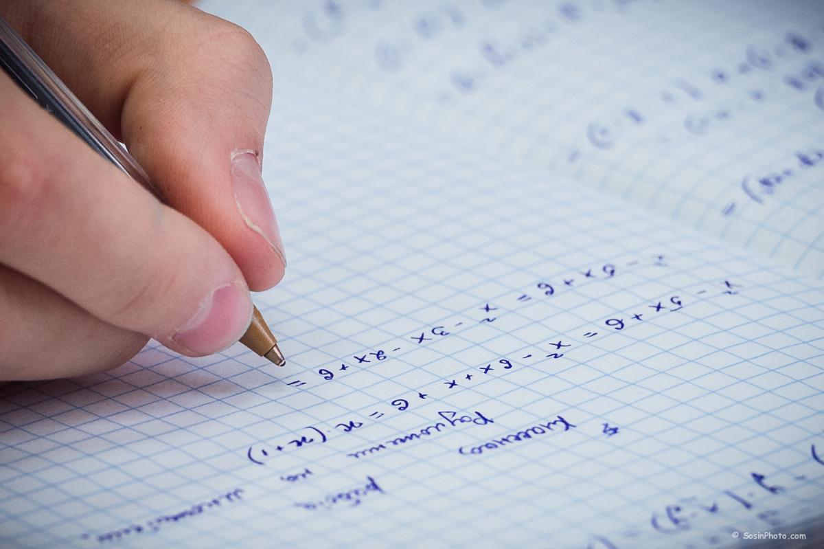 школьник пишет в тетради по математике